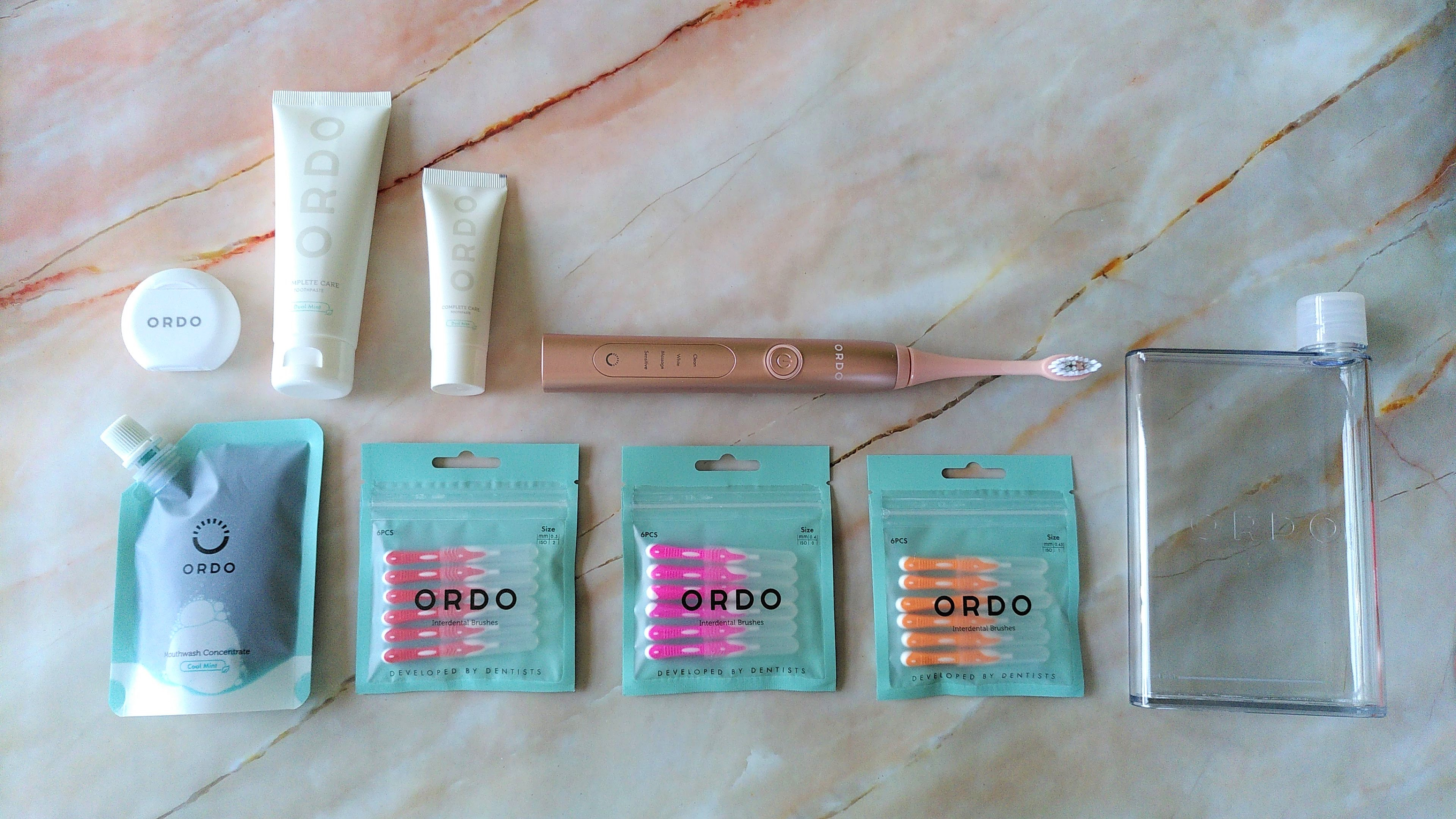 Ordo Sonic+ electric toothbrush with mouthwash concentrate, interdental brushes, floss, toothpaste, and reusable mouthwash bottle