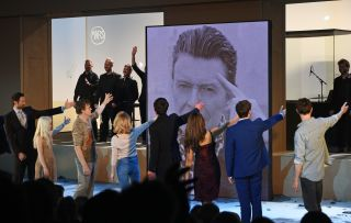 """From left, cast members Tom Parsons, Sophia Anne Caruso, Michael C Hall, Amy Lennox, Michael Esper, Julie Yammanee and Jamie Muscato pay tribute to playwright David Bowie at the curtain call during the press night performance of """"Lazarus"""" at the King's Cross Theatre on November 8, 2016, in London."""