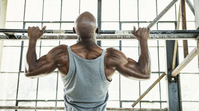 The best pull up bars can help you a big back, as big as this person has who's performing a wide grip pull up using a wall-mounted pull up bar