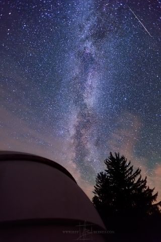 A Perseid meteor crosses the Milky Way in the night sky above an observation dome at Cherry Spring State Park.