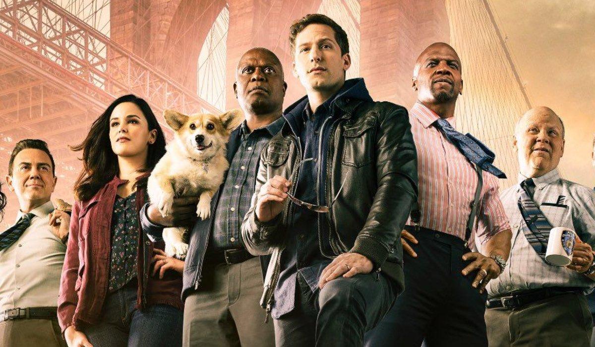 The cast of Brooklyn Nine-Nine stands triumphantly under the Brooklyn Bridge.