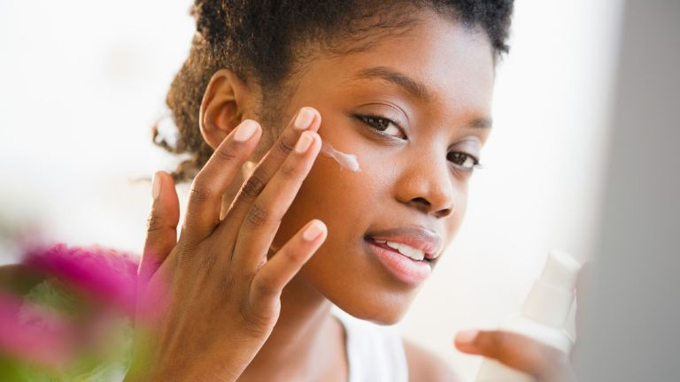 Woman putting on face cream