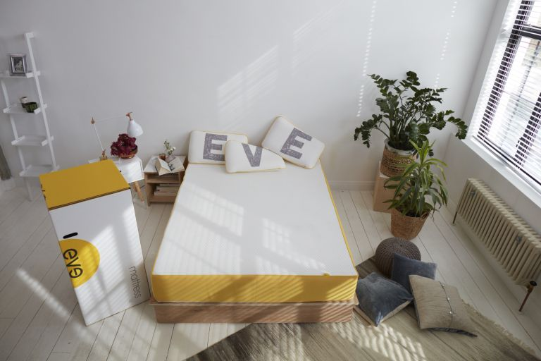 Eve mattress review: Eve mattress on bed with pillows spelling EVE