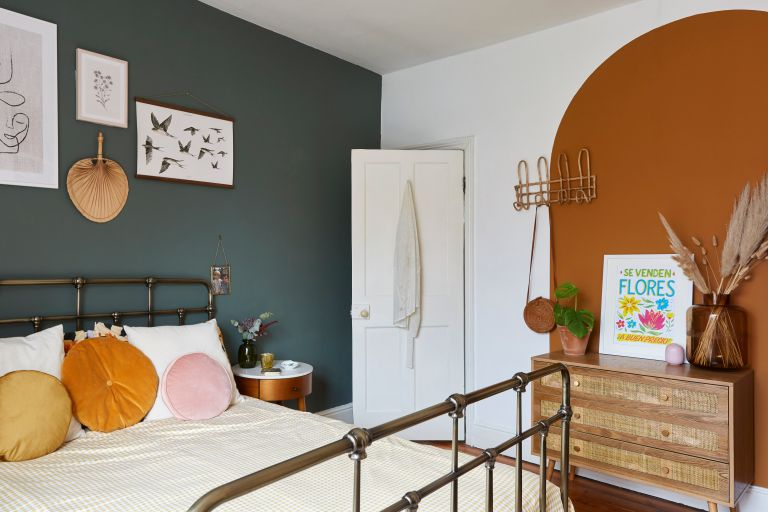 master bedroom with one dark wall and an orange painted arch with rattan furniture and a black metal bed
