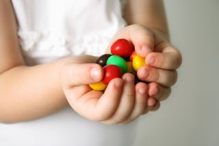 A little girl holds a handful of candy
