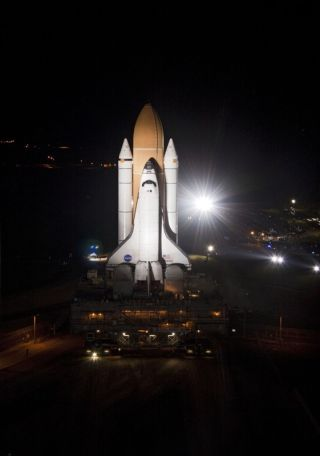 Bright xenon lights flare while space shuttle Atlantis rolls down a 3.4-mile stretch of river rocks, as the vehicle embarks on its historic final journey from the Vehicle Assembly Building to Launch Pad 39A at NASA's Kennedy Space Center in Florida, on Ma