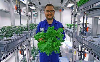 Paul Zabel holds veggies grown in the EDEN ISS greenhouse in Antarctica.