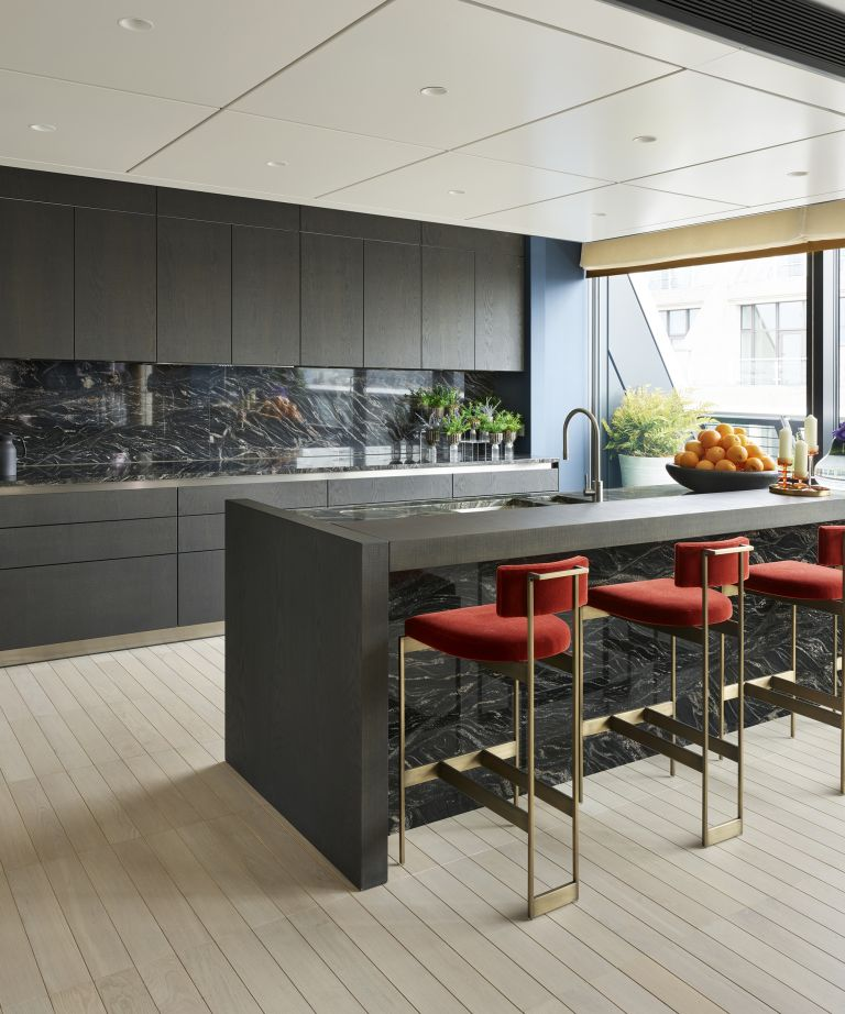 dark kitchen with red dining chairs