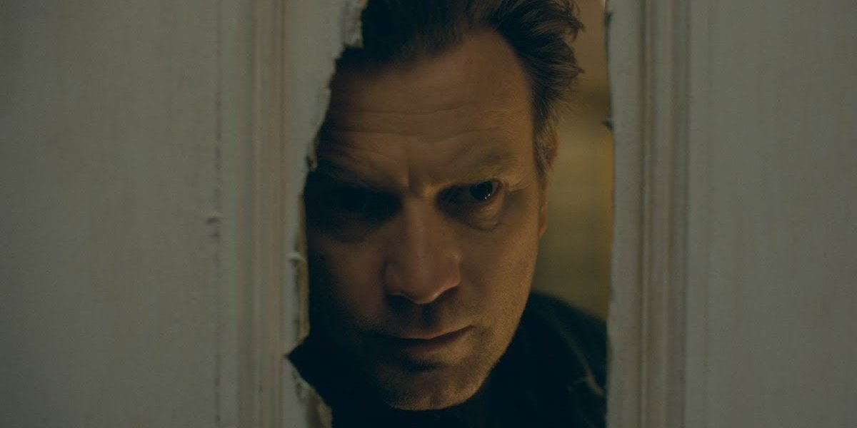 Doctor Sleep Ewan McGregor peeks into a door's hole