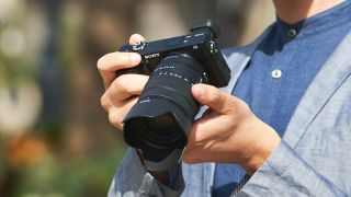 A man holding the Sony a6100, our top pick of the best mirrorless cameras