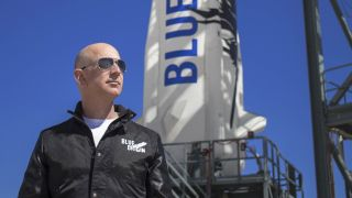 Jeff Bezos at the Blue Origin launch pad with a New Shepard rocket in the background.