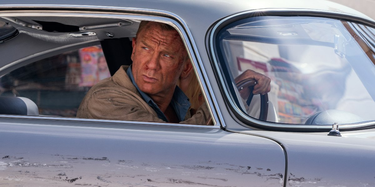 Daniel Craig glares while driving a damaged DB5 in No Time To Die.