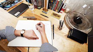 Hand using Rotring pen in sketchbook - best Rotring pen