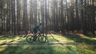 Does bike riding build your glutes? Man riding a bike through a forest
