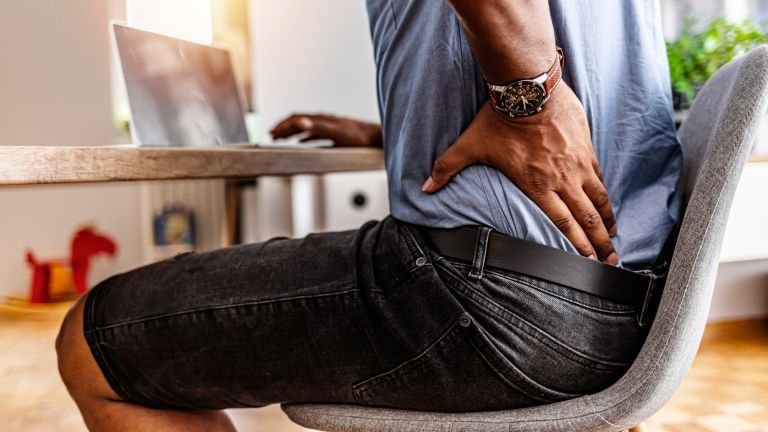 Man supports his lower back with hand as he sits at a table doing work