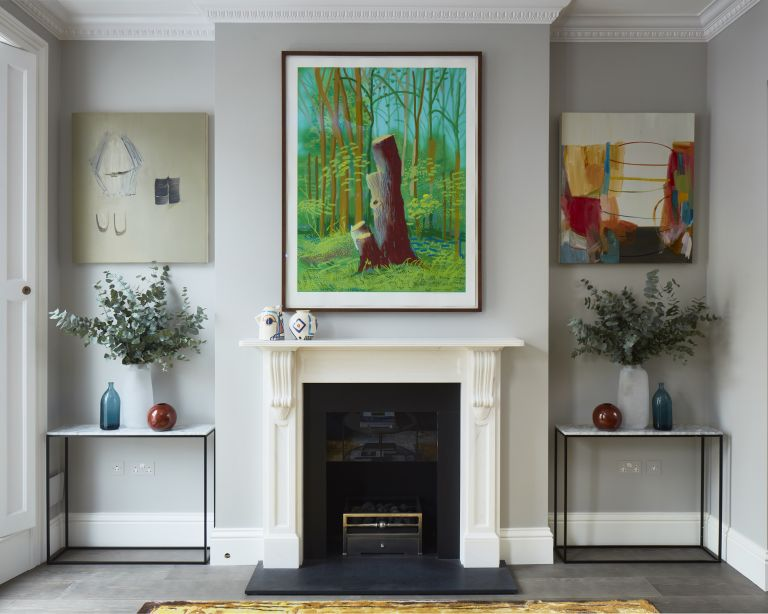 A pale gray living room with a white fireplace and three large artworks hung on the wall