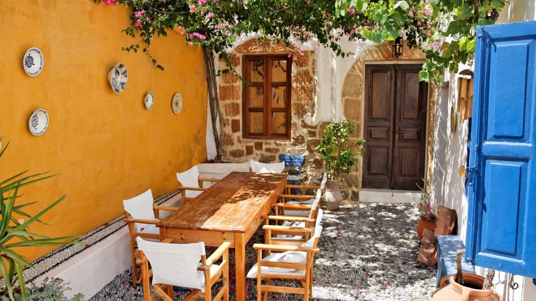greek garden ideas – yellow courtyard with pergola and dining set