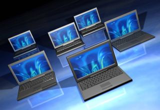 Multiple laptop computers arrayed on a reflective glass-like surface.