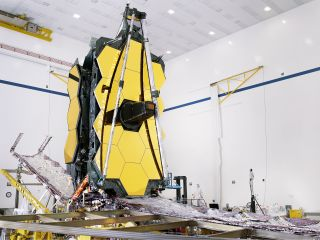 "The fully assembled James Webb Space Telescope with its sunshield and ""unitized pallet structures"" (which fold up around the telescope for launch) are seen partially deployed to an open configuration to enable telescope installation."