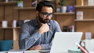 Man watching video on his laptop in office