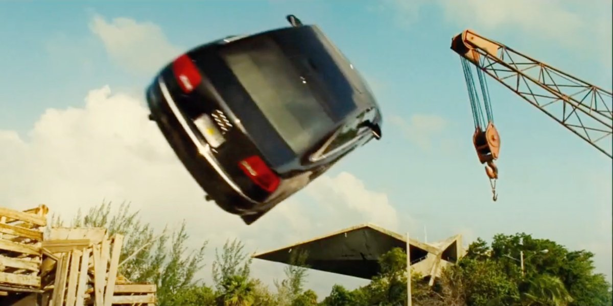 Jason Statham driving a car towards a crane in Transporter 2