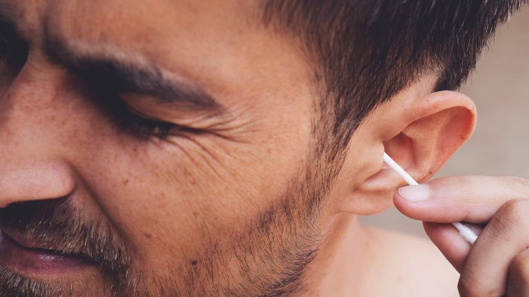 Man trying to clean his ears with a cotton bud