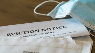open eviction notice on table with surgical mask lying nearby