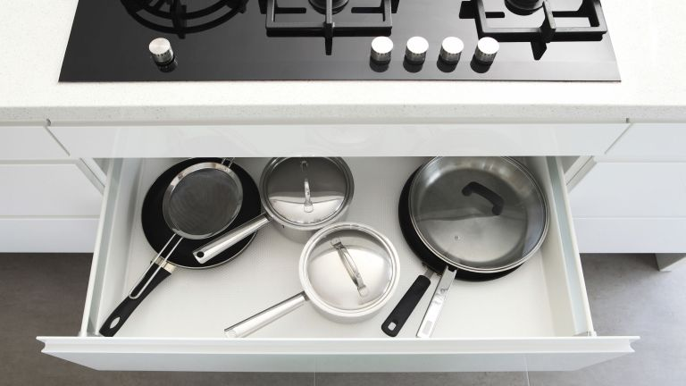 pots and pans in a drawer below the hob