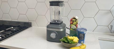KitchenAid K150 blender on a kitchen countrop with a pile of fruit and vegetables ready to be made into a smoothie