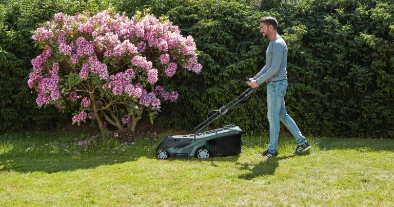 Best lawnmowers: Lifestyle image of man using Bosch lawnmower