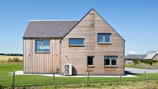 a timber clad self build home with an air source heat pump