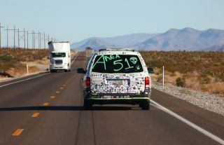 """A car drives with """"Area 51"""" written on the back before the start of a """"Storm Area 51"""" spinoff event called """"Area 51 Basecamp"""" on September 20, 2019 near Alamo, Nevada."""
