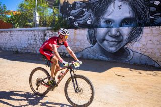 Todd Wells rides past a mural
