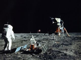 Apollo 11 astronaut Buzz Aldrin unpacks a seismic experiment on the surface of the moon.