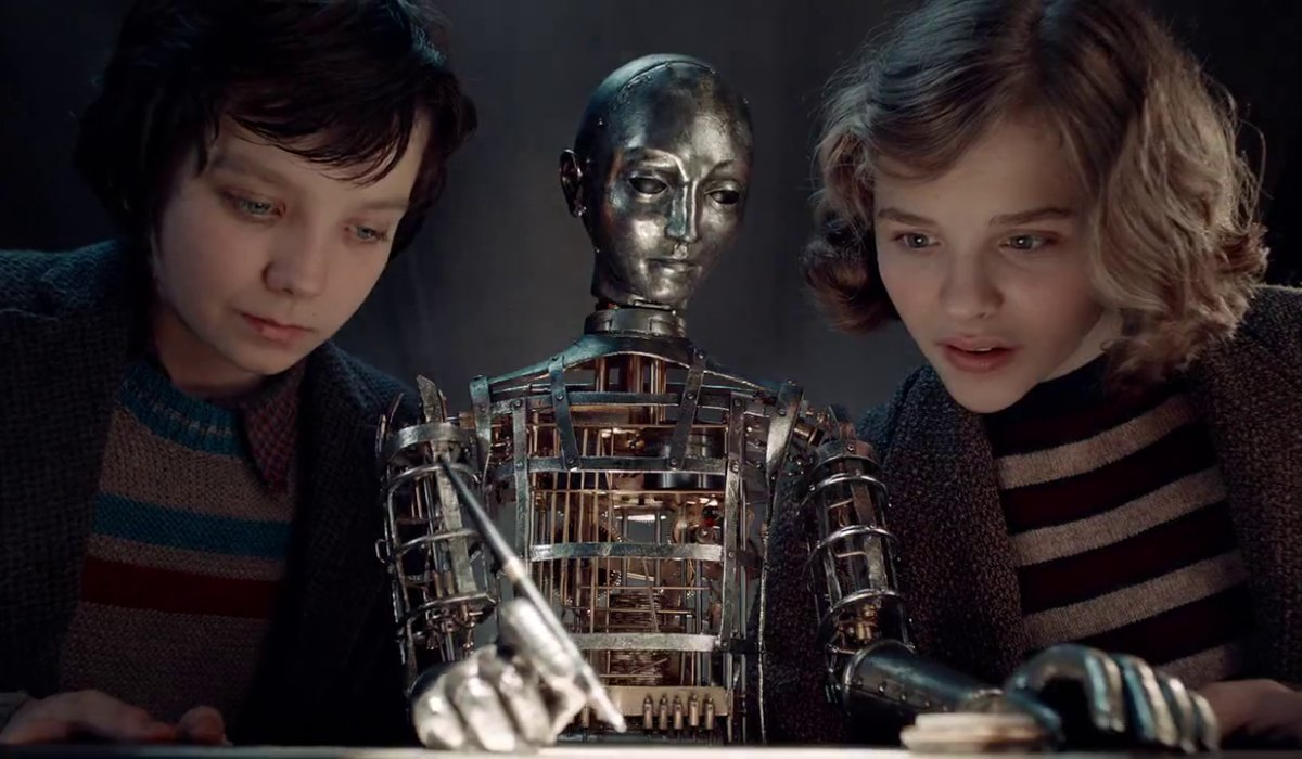 Hugo Asa Butterfield and Chloe Grace Moretz study the drawing machine