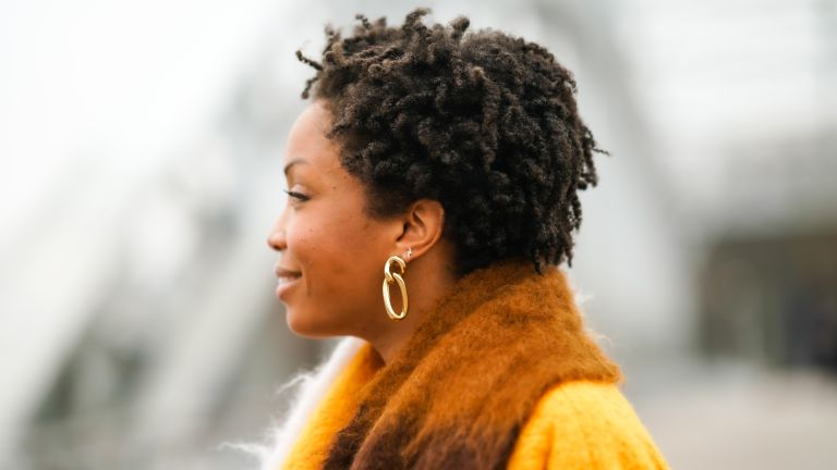 Ellie Delphine wears golden earrings, a multi colored wool Loewe scarf, an orange wool coat with from Mariam Al Sibai, on January 06, 2021 in Paris, France.