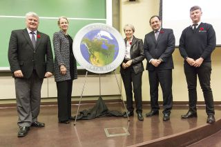 Five people pose with a large model of a colorful coin with a map of Canada on it