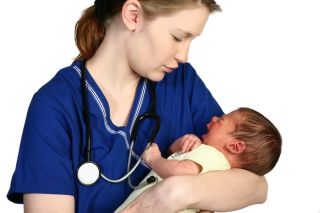 A nurse cradles a baby.