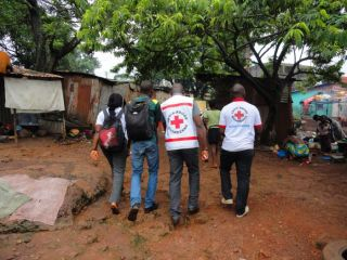 Guinean Red Cross volunteers making their way door-to-door, sharing information about Ebola during the 2014 outbreak.