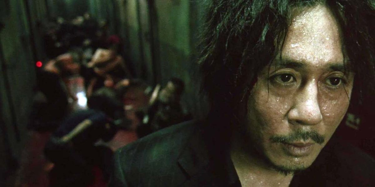 Oh Dae-su (Choi Min-sik) after punching and kicking through a hallway in Oldboy