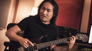 A portrait of Herman Li with guitar