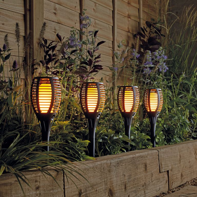 Best solar lights: solar ground lights with a flickering flame effect in a flower bed