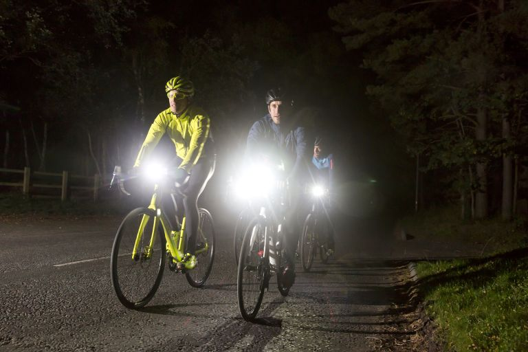 Group of cyclists riding on an unlit road with bike lights