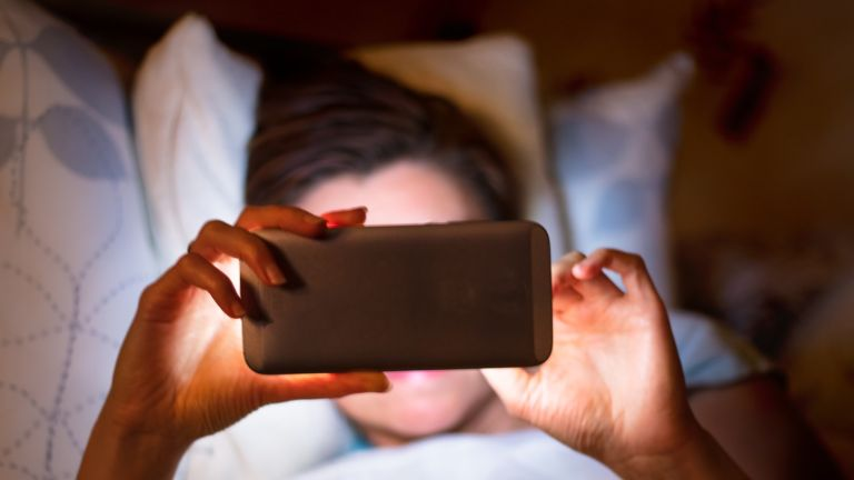 Woman addicted to tracker in bed reading phone night time
