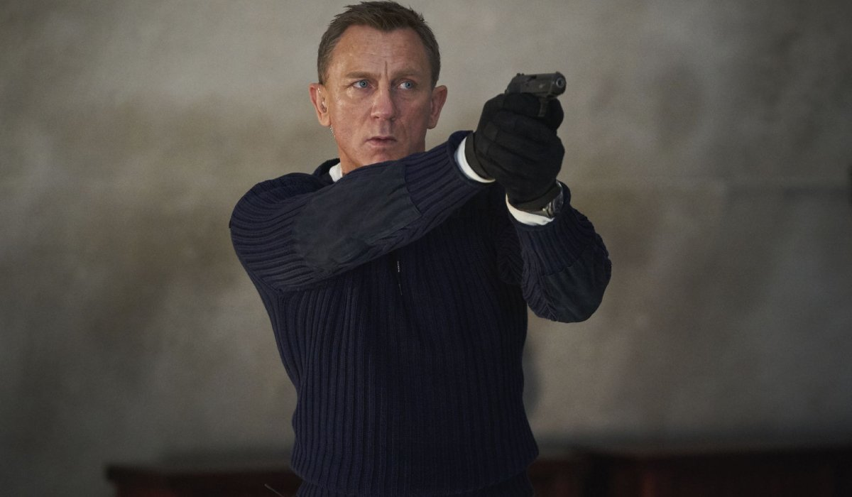No Time To Die Daniel Craig aims his pistol in a sweater