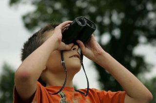 Best binoculars for kids: Image shows boy looking through binoculars