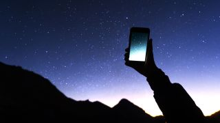 Best stargazing apps: Image shows person holding mobile up to starry night sky