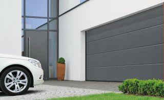 A grey garage door on a white garage