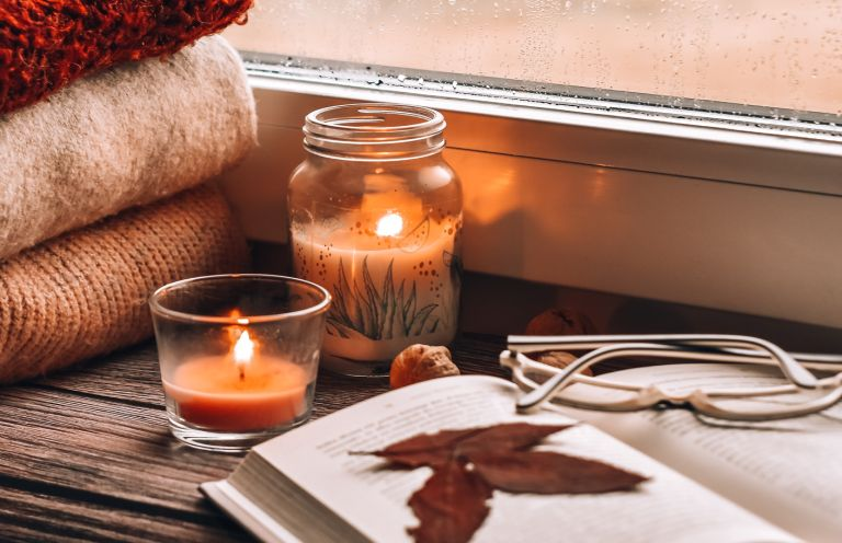 Close-Up Of Lit Candles On Table At Home