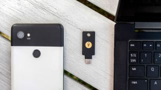 A YubiKey 5C NFC resting on a wooden surface alongside an Android phone and a laptop.